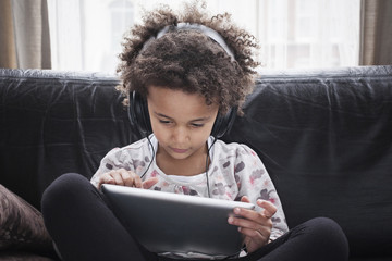 Girl sitting on sofa using digital tablet and headphones