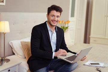 manager sitzt im hotel auf dem bett und arbeitet am laptop
