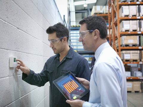 Factory and office workers checking thermostat in factory