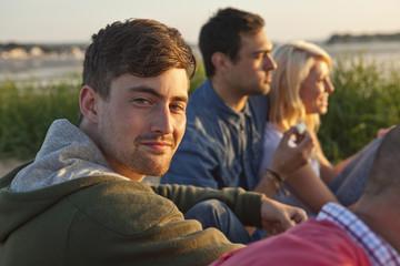 Four adult friends sitting on Bournemouth beach, Dorset, UK