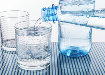 Mineralwasser aus blauer Flasche in ein Glas eingeschenkt