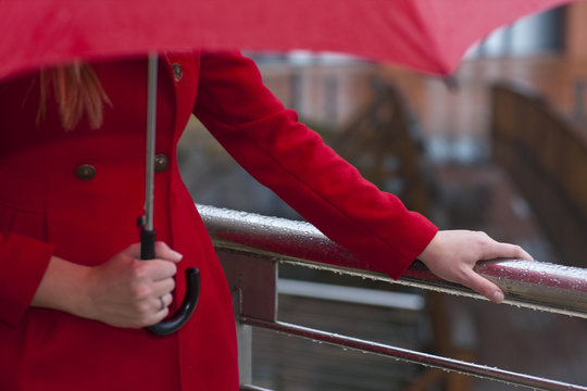 Cropped image of young woman in red carrying umbrella