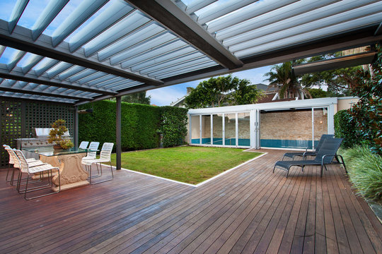 a beautiful courtyard with a lawn and swimming pool . barbecue area .
