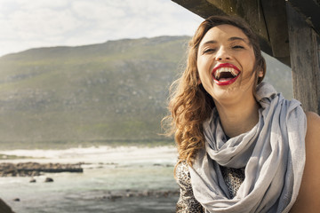 Young woman laughing on coastal pier, Cape Town, Western Cape, South Africa