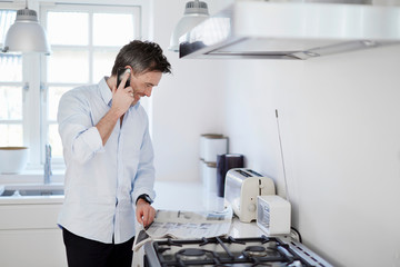 Man standing in kitchen making phone-call and reading newspaper