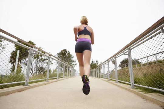 Low angle view of woman running on bridge