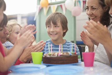 Mother and group of children enjoying birthday party