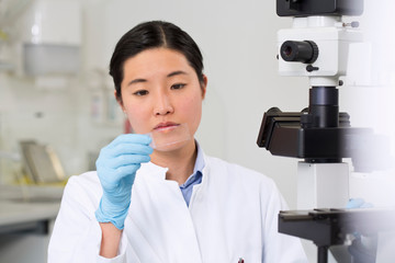Female scientist working in laboratory with microscope