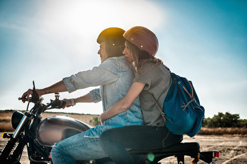 Mid adult couple motorcycling on arid plain, Cagliari, Sardinia, Italy