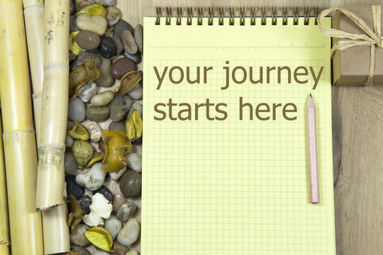 your journey starts here writing in notebook. paper envelope with a pen, wooden desk