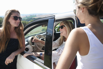 Mature woman sitting in car, talking to teenagers