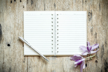 Blank notebook with orchids purple flowers on wooden table.