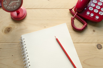 Red Desktop, Red telephone and Red clock on wooden table with notebook, All Item is red, Selective Focus