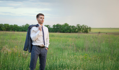 Businessman standing in field and looking forward