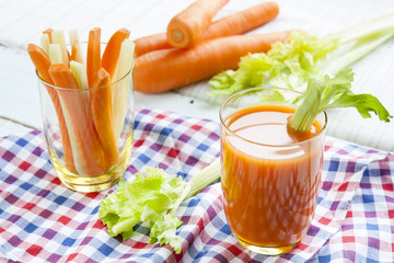 Fresh carrot juice with carrots and celery on checkered napkin light background