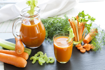 Fresh carrot juice with carrots, celery, dill and parsley on black background