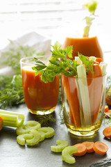 Fresh carrots and celery in glass with fresh carrot juice, dill and parsley on black background
