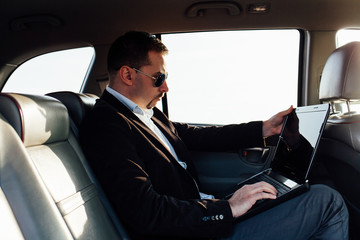 Businessman using laptop on the backseat of luxurious car