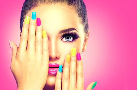 Beauty girl face with colorful nail polish