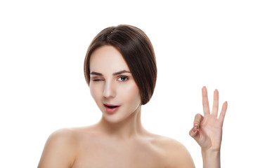 Pretty girl with natural makeup show gesture OKEY. Beautiful spa woman touching her face. Perfect fresh skin. Pure beauty model girl. Youth and skin care concept