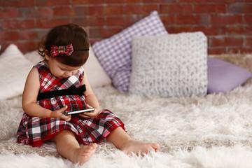 Little girl watching smartphone on the sofa