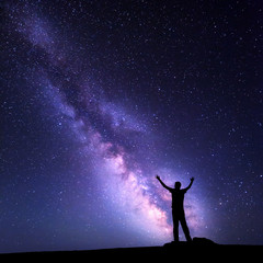Landscape with colorful purple Milky Way. Night sky with stars and silhouette of a happy man with raised up arms on the mountain. Beautiful Universe. Space background
