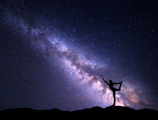 Landscape with purple Milky Way. Colorful night sky with stars and silhouette of a standing sporty girl with raised-up arms on the mountain. Beautiful Universe. Space background