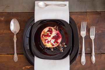 Half of pomegranate on a black plate lying on a festively decorated table on top view