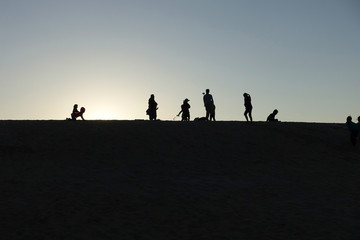 Silhouette of a large family taking pictures, relaxing on the top of a sand dune.