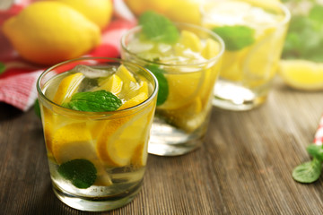Composition of lemonades,  lemons and mint on wooden table background, closeup