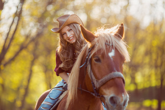 Beautiful smiling girl riding horse on autumn field