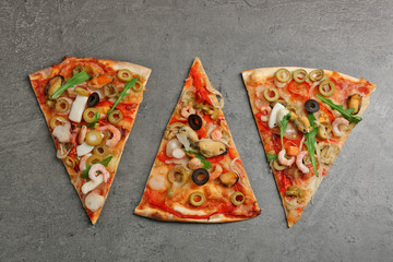 Pizza slices with seafood, red pepper and olives on grey background