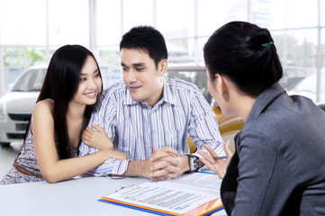 Car buyers discussing with car dealer
