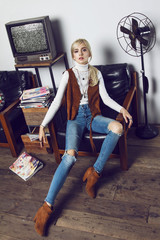 Beautiful young blond girl wearing cowboy clothes and posing like a doll. She is captured in nice scene with old TV, phone, furniture, magazines, table, pictures, dartboard and fen.