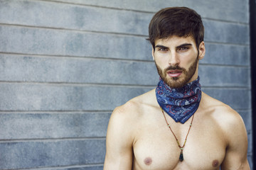 Close up of handsome man with long beard and blue scarf around his neck.