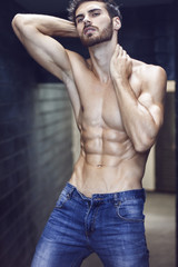 Close up of handsome man with long beard. He is posing in front of camera just with open jeans and showing his muscles. Abdominal dominant part.
