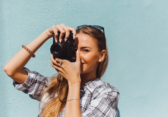 Closeup young beautiful stylish hipster girl, denim outfit, positive mood, cool vintage style, having fun, sitting, wall background, oldschool film camera, take photo, hands holding, blond, smiling