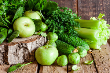 green organic fruit and vegetables on a wooden background