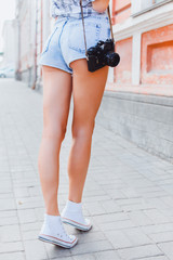 Outdoor crop foot of tanned slim woman with camera,travel photo.Adventure,hiker,sneakers,shorts,old city street,freedom concept. Making pictures in hipster style glasses