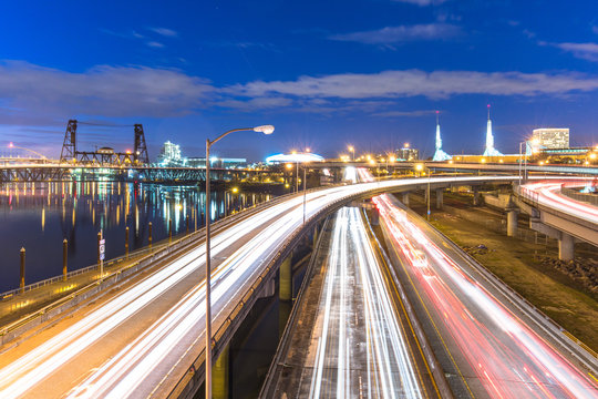 traffic on road with cityscape and skyline of portland at twilig