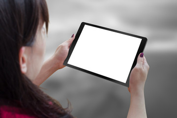 Black tablet with blank, white, isolated screen for mockup in woman hand. City life in background.