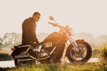 young brutal man in a black jacket and glasses standing near a motorcycle