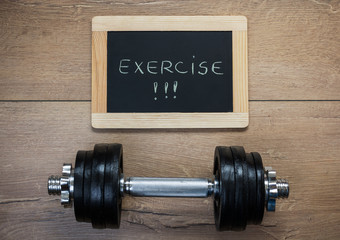 Concept for exercise and sport. Dumbbell and a message on a chalkboard on a wooden background