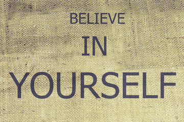 The text believe in yourself on brown burlap. Retro burlap background. vintage
