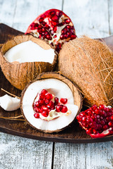 Fresh coconut and red garnet in a wooden bowl,blue background