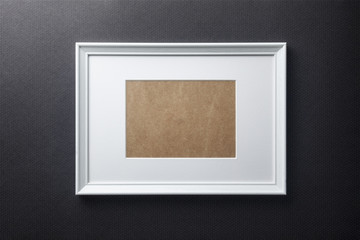 White plain empty wood picture frame with white mat passe-partout on black bricks background