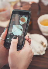 Woman's hand with smartphone taking food photo for instagram