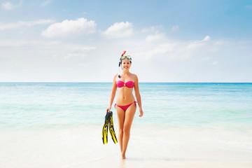 Beautiful, smiling girl in pink bikini diving in the sea