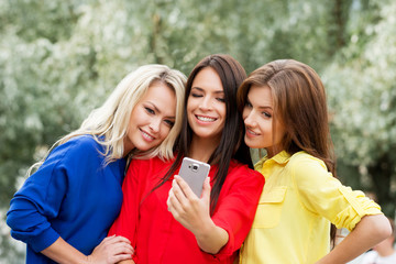 Group of gorgeous girls taking selfies in the park