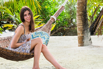 Young smiling lady relaxing in hammock on tropical beach among palms